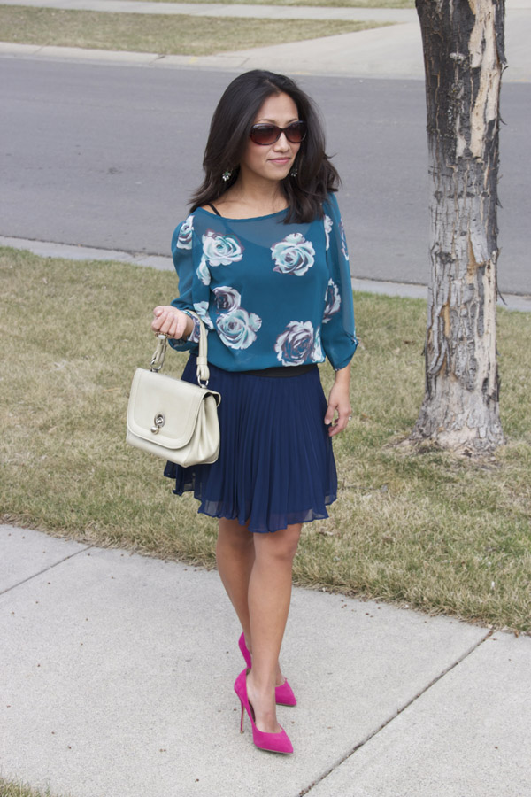 A teal floral print top with a navy blue pleated skirt