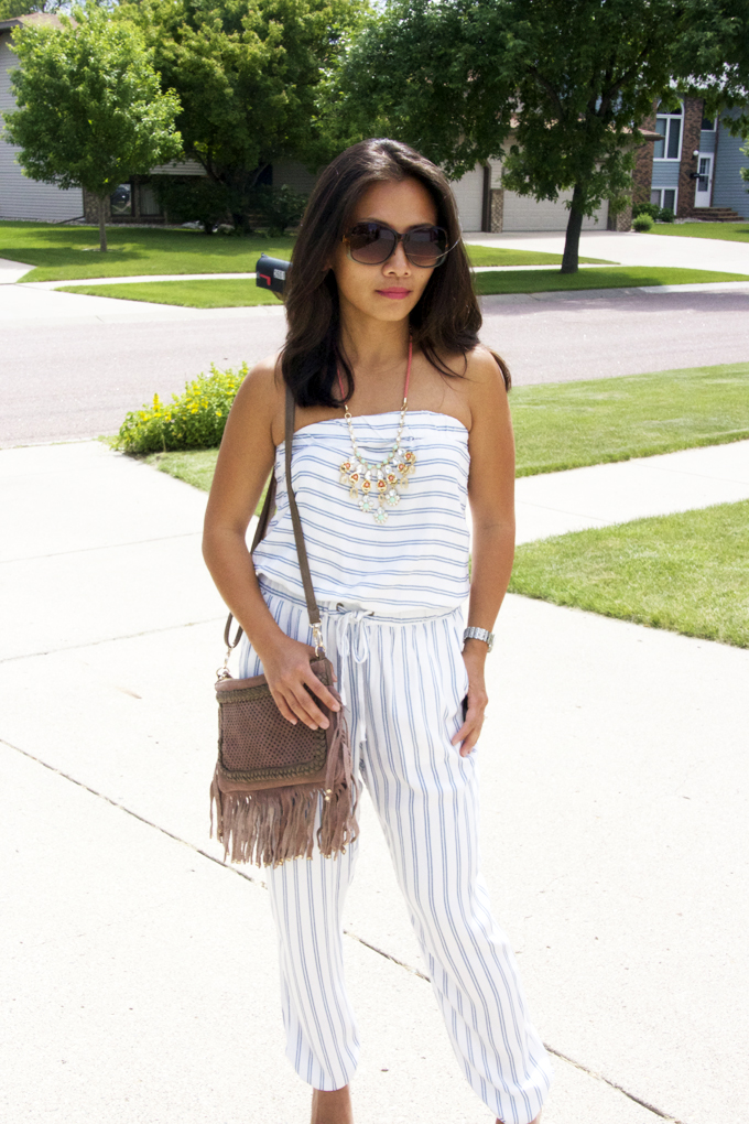 This is a picture of a striped jumpsuit look with fringe bag