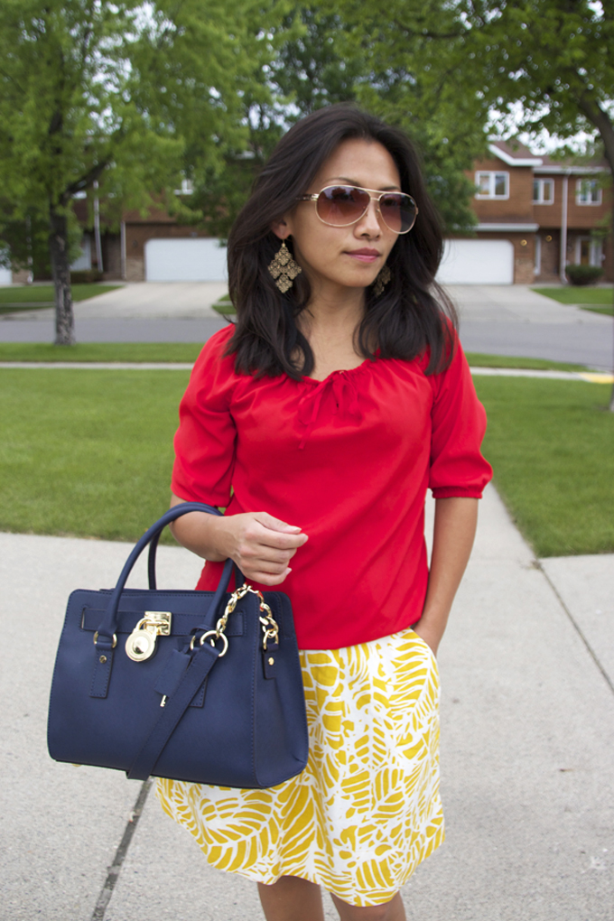 This is a look of a casual tangerine red top and a citron stenciled skirt.
